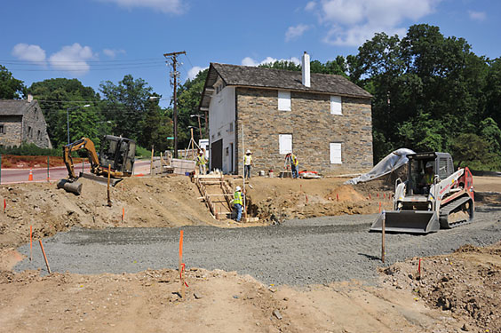 A tractor levels gravel to recreate the historic millyard between the mill and the carriage house in June 2011.