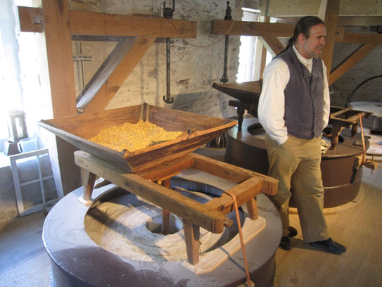 The hopper filled with corn sits just above the millstones.