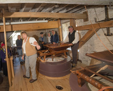 Volunteers assist miller Jeanne Minor in operating the mill.